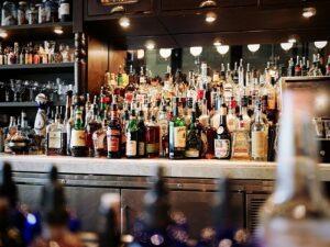 酒場の内部。カウンターに酒瓶が並ぶ。