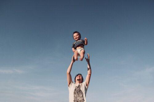 子供を宙に投げて遊ばせる父親。