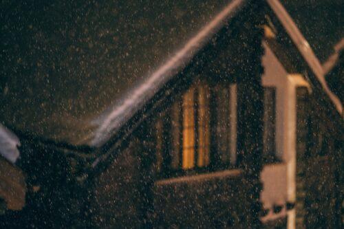 夜の家の窓に灯がともっている。