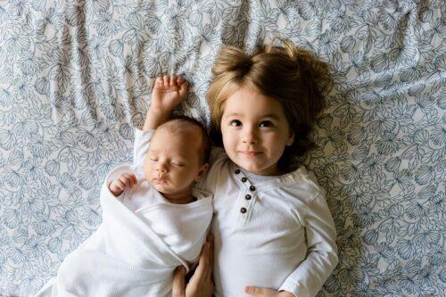 赤ちゃんと添い寝する幼い少女。