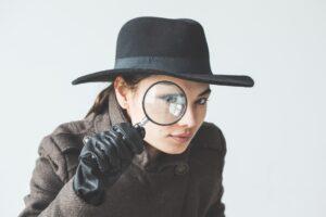虫眼鏡で調べる女性探偵。
