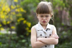 不満のあまり腕組みをする少女。